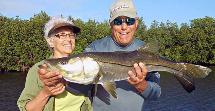 freindly tampa fishing charters client with guide holding snook